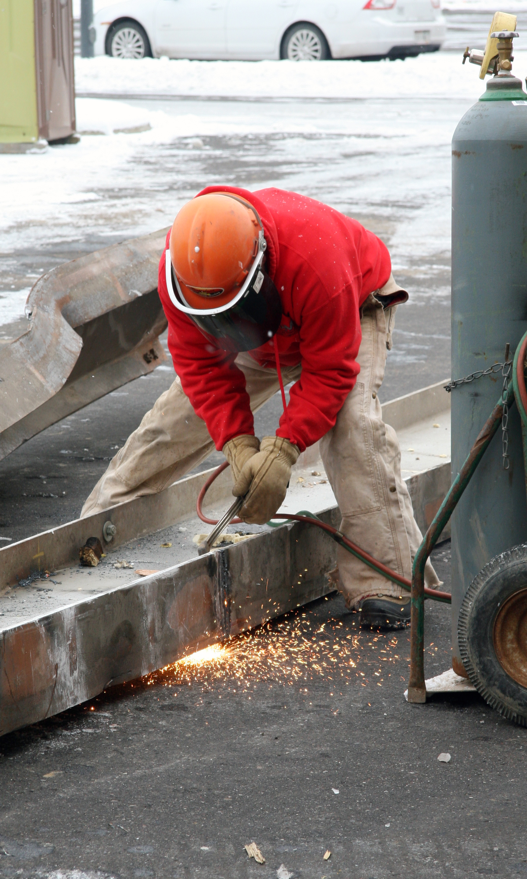 Crew member cutting a beam in two so that it can fit in the rolloff for recycling